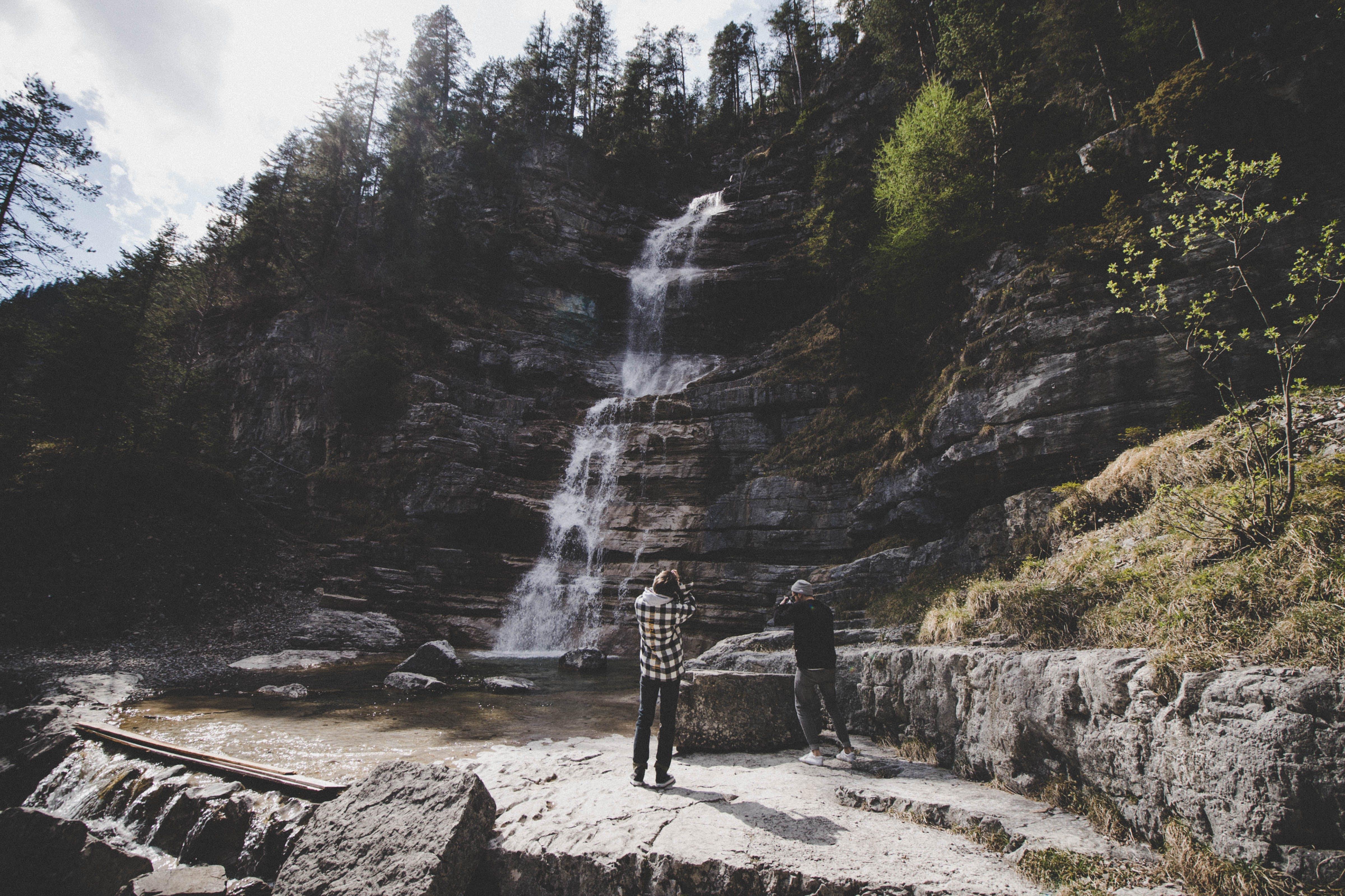 Two Man Taking Photo of Waterfalls