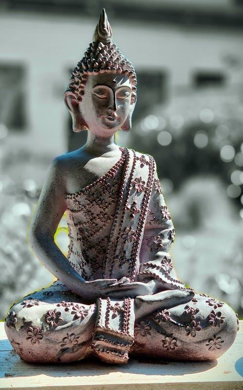 Old stone sculpture of Buddha in traditional clothes with decorative head wear on wooden bench
