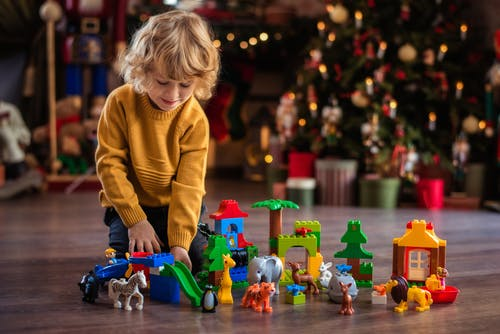 Girl in Yellow Sweater Playing With Lego Blocks