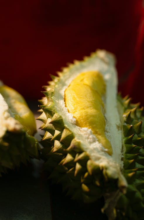 From above of slice or bright ripe exotic fruit with strong smell and prickly peel on brown background