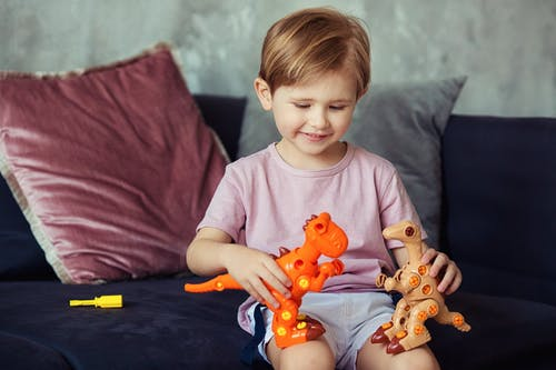 Cute Boy Sitting on a Sofa Playing with His Dinosaur Toys