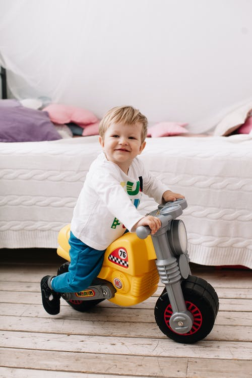 A Child Riding on His Plastic Toy   Motorbike