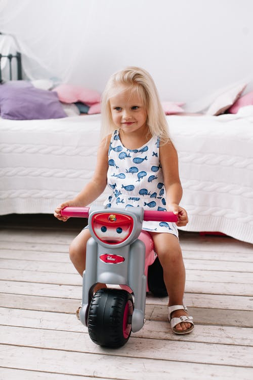 A Cute Girl Riding on Her Plastic Toy Motorbike