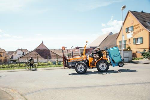 Základová fotografie zdarma na téma asfalt, dělník, denní světlo, domy