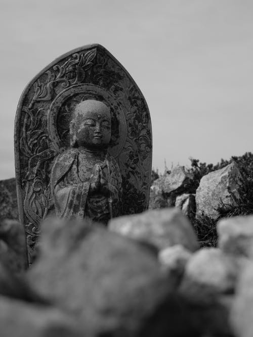 Black and white of aged sculpture of Buddha with ornament near rough stones under sky