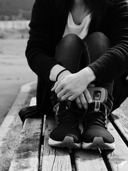 Black and white of crop unrecognizable female in casual wear and sneakers sitting on old bench near pavement in city