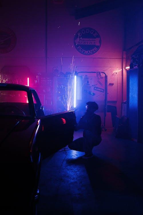 Man in Black Jacket Sitting on Black Car