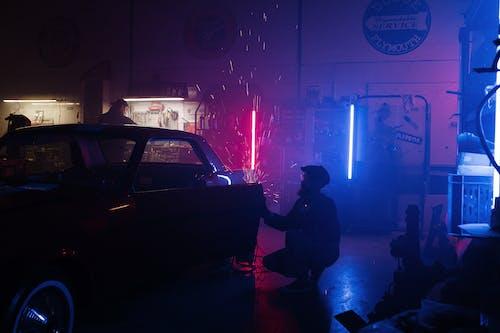 Man in Black Jacket Standing Beside Black Car during Nighttime