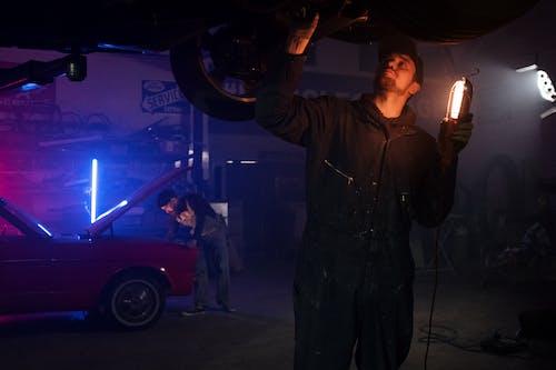 Man in Black Leather Jacket Holding Black Car Steering Wheel