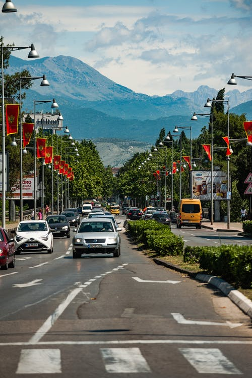 City road with driving cars behind mountains