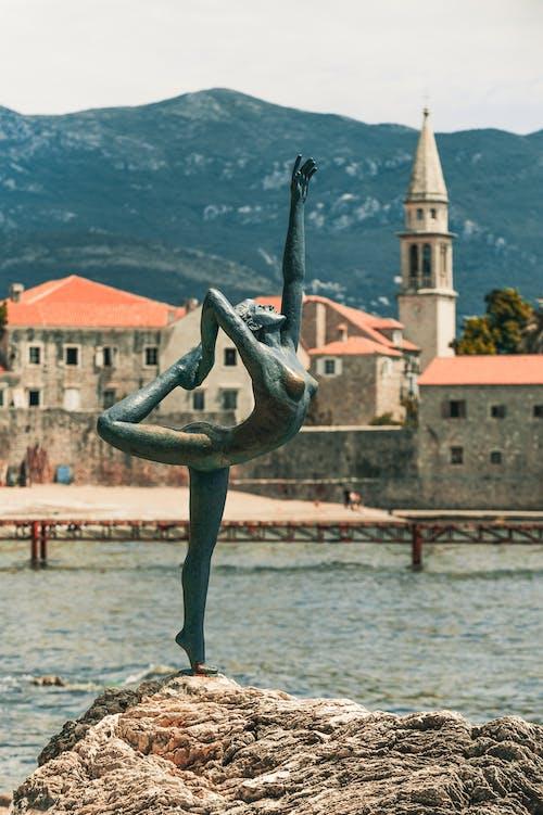 Statue of ballerina near sea and old house facades