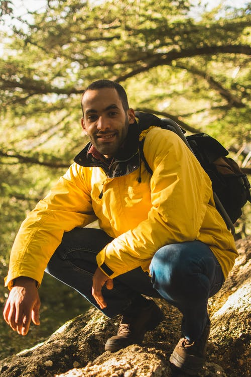 Man in Yellow and Black Jacket Sitting on Brown Tree Log