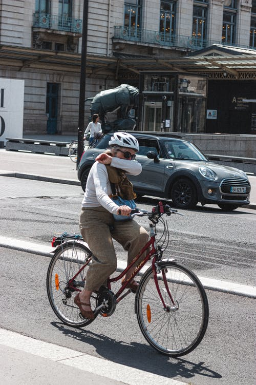 Anonymous old woman riding bicycle on city street