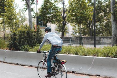 Faceless man riding bicycle along sunny street