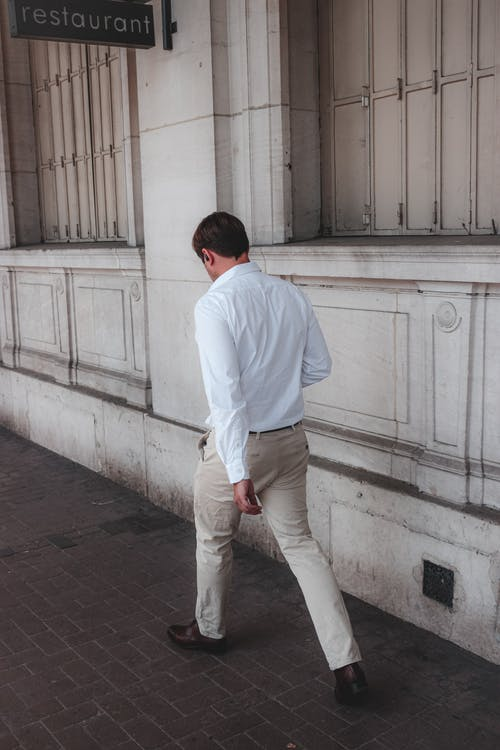 Back view full length male wearing light smart casual outfit and walking along paved walkway in daylight