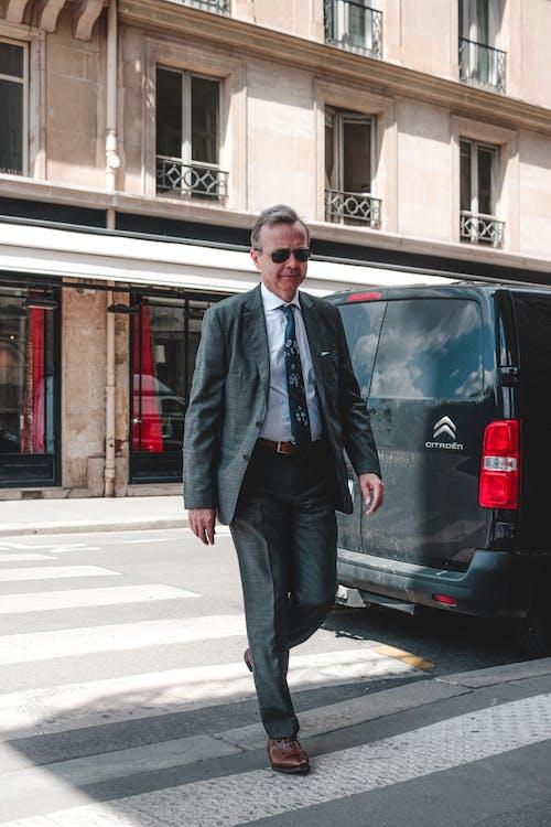 Positive man walking on pedestrian crossing