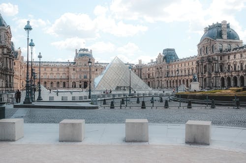 Exterior of historic Louvre Museum build in Gothic style near famous landmark glass Pyramid located in center of Paris on summer day