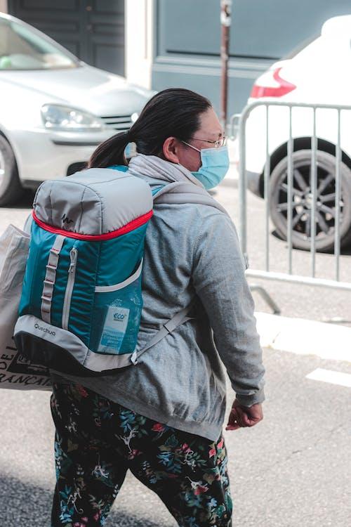 Plump pedestrian in face mask on roadside