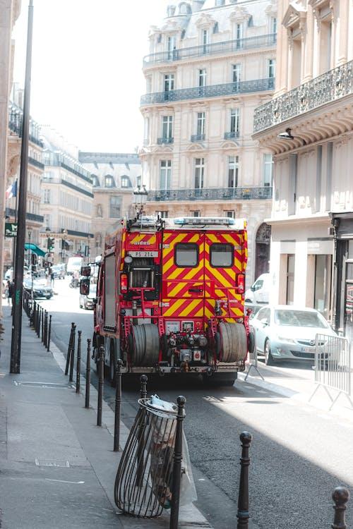 Fire engine truck driving along narrow busy street