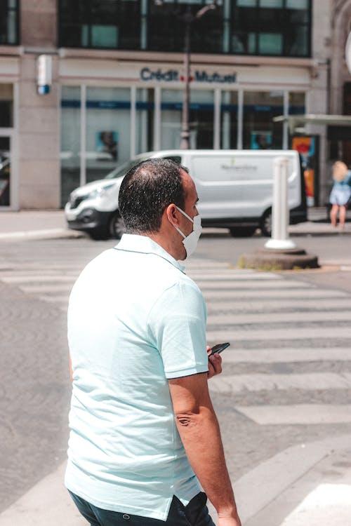 Faceless man in respirator walking on street sidewalk