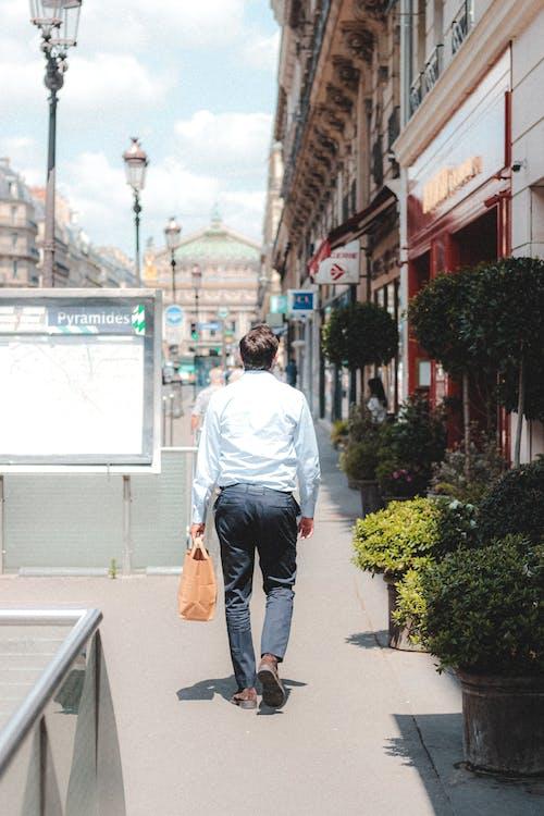 Unrecognizable man walking along street sidewalk