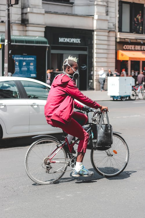 Black man in respirator riding bicycle on busy street