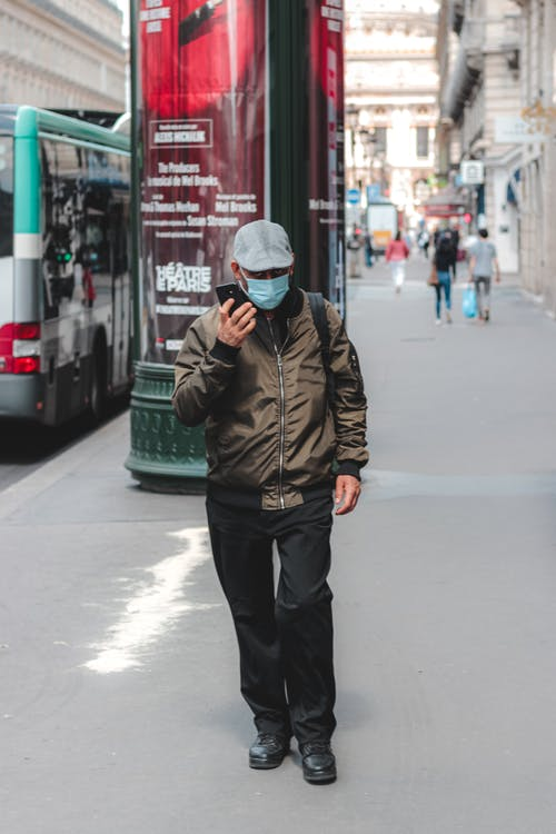 Full body faceless male in casual clothes and face mask walking on asphalt walkway in busy city district and using mobile phone