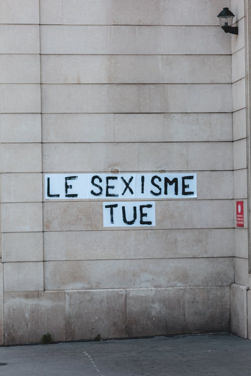 Inscription Le Sexisme Tue in French language written with black letters on white background on modern building wall