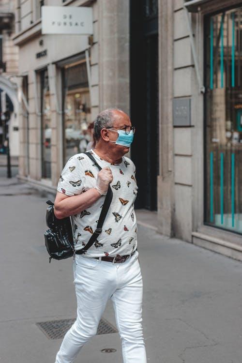 Stylish man in protective mask and gloves strolling along sidewalk