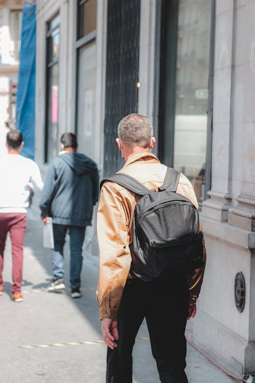 Unrecognizable man walking along sunny street sidewalk
