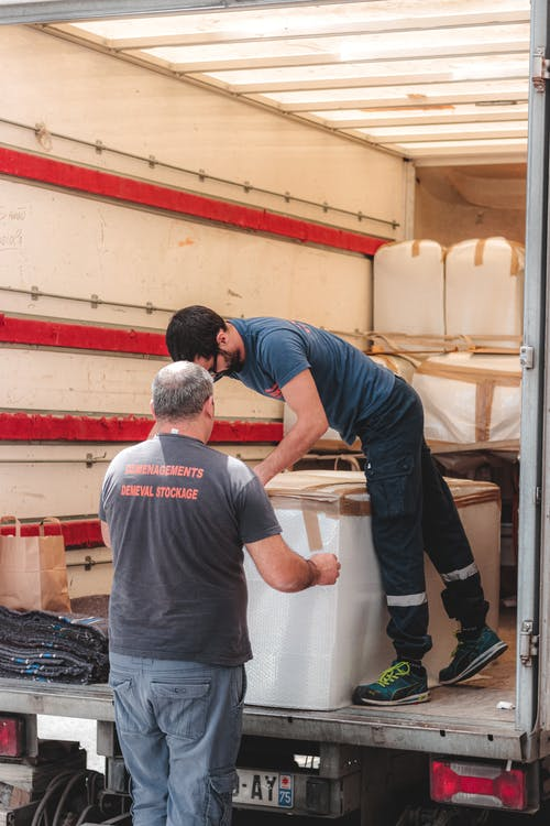 Removal porters unloading truck with big boxes