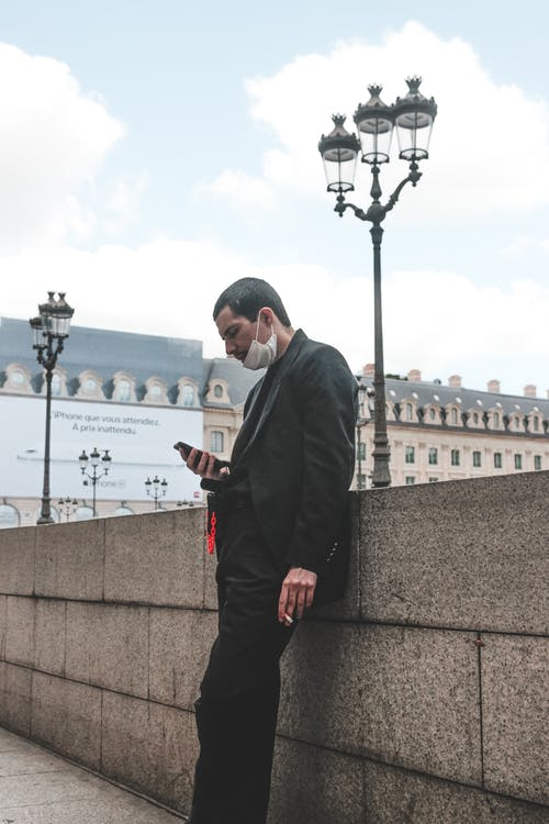 Ethnic man in face mask using smartphone and smoking