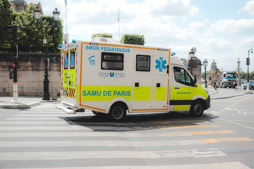 Ambulance driving along road in sunny city