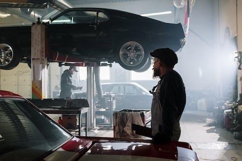 Man in Black Jacket Standing Beside Car