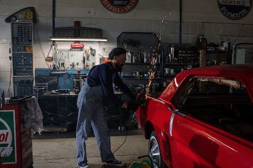 Man in Blue Dress Shirt Standing Beside Red Car