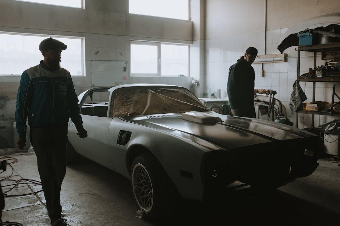 Man in Black Suit Standing Beside Silver Porsche 911
