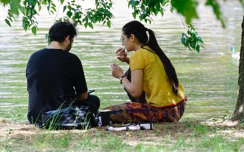 Δωρεάν στοκ φωτογραφιών με άνοιξη, κάθονται στο γρασίδι, λίμνη, νεαρό ζευγάρι