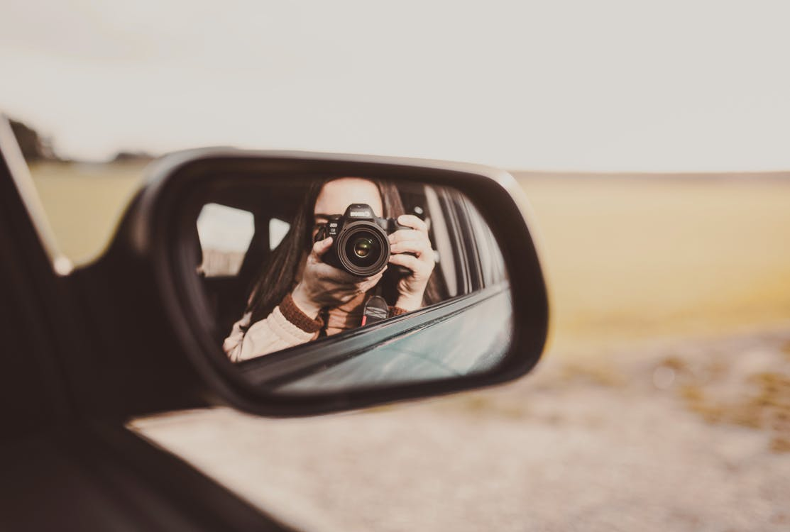 Person Taking Photo of Car Side Mirror