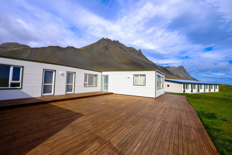Mountain Across Houses on Green Grass Field Under Clear Blue Sky
