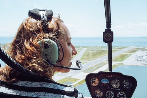 Back view of positive young female traveler in casual wear and headset sitting in cockpit of modern helicopter during flight over coastal town