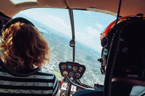 Back view of unrecognizable travelers in headsets admiring view of city during flight in helicopter