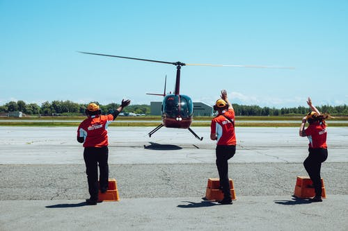 Back view of anonymous ground crews in uniforms and headsets meeting passenger helicopter on airfield after flight against cloudless blue sky