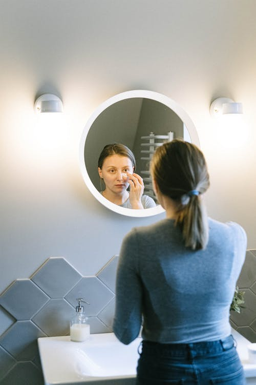 Woman in Gray Sweater Standing in Front of Mirror
