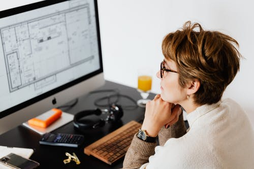 Serious woman reading information on computer monitor while working in modern office