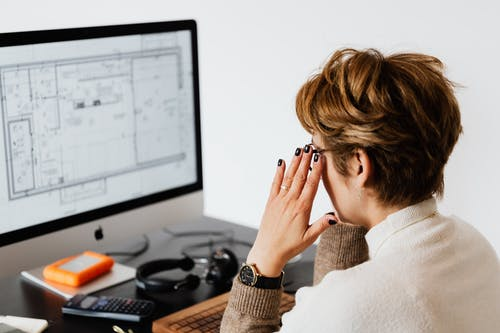 Side view of unrecognizable short haired woman wearing eyeglasses while reading documents on computer monitor during work in light office