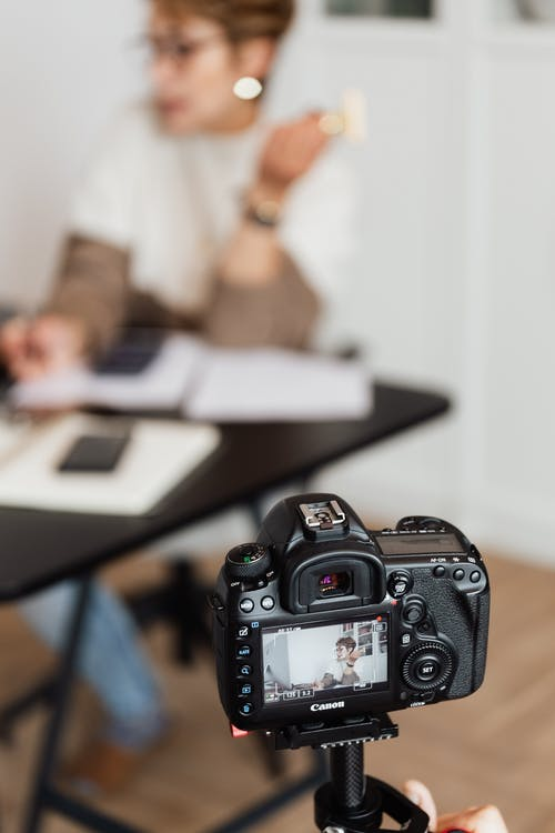 Anonymous person taking photo of busy unrecognizable woman on professional camera during work in modern studio