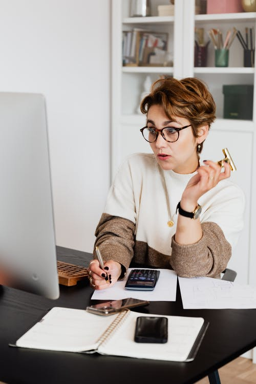 Surprising adult short haired female employee in eyeglasses reading unexpected information on computer and taking notes