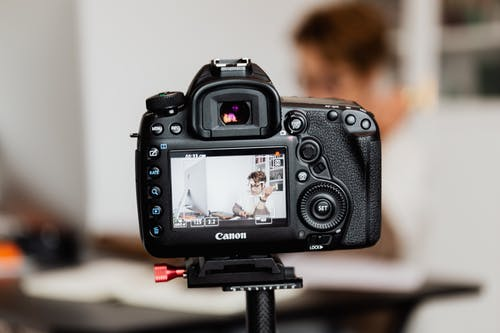 Photo camera recording vlog in modern workspace