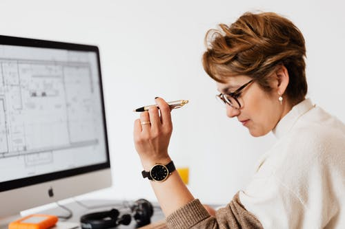 Concentrated adult female thinking about business project in office