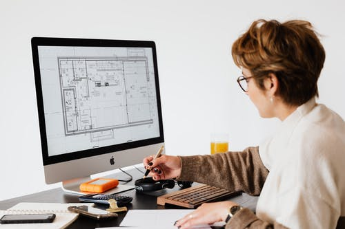 Side view of anonymous female employee in casual clothes and eyeglasses writing out information from computer while working at table in modern light office